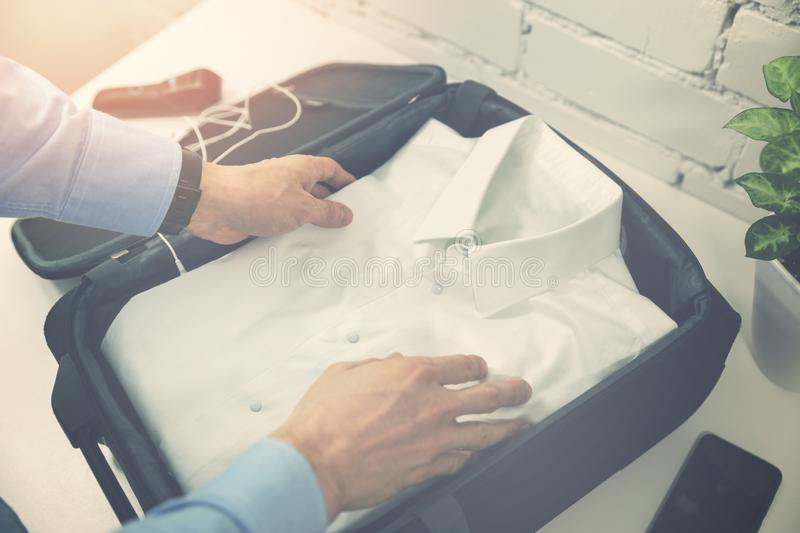 Man packing travel suitcase for business trip royalty free stock images