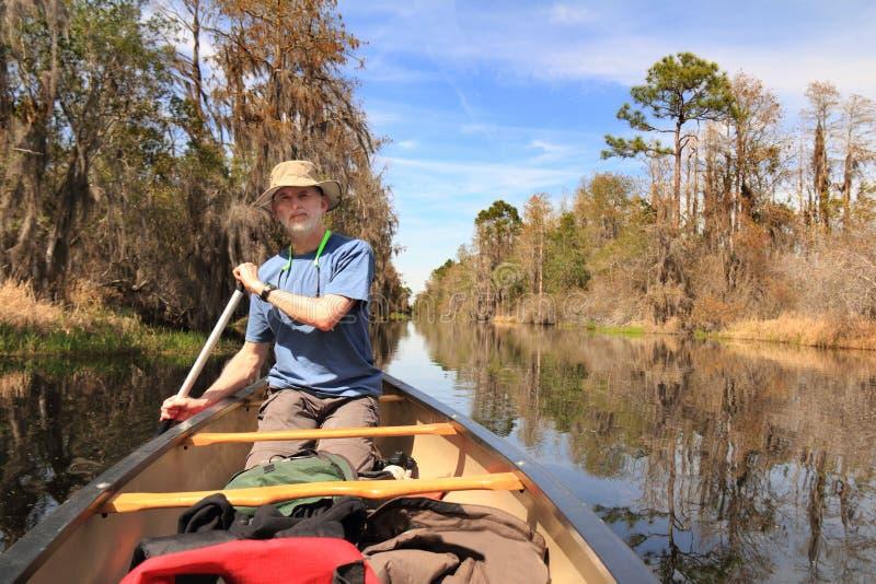 Man Paddling a Canoe - Okefenokee Swamp. Man Paddling a Canoe on the Suwanee River - Okefenokee Swamp, Georgia royalty free stock image