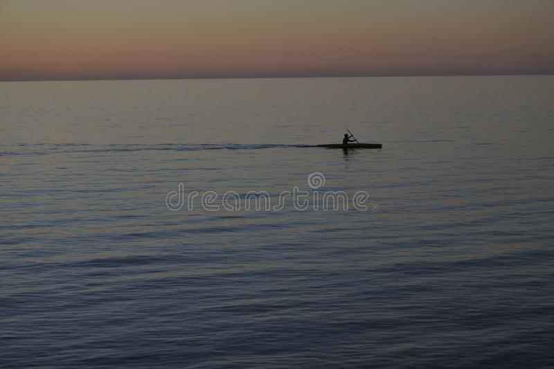 Man paddling in kayak with dramatic sunset royalty free stock photography