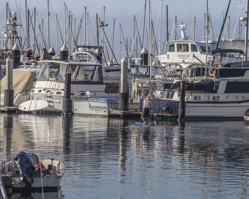 Man paddling near luxury boats at Santa Barbara marina royalty free stock image