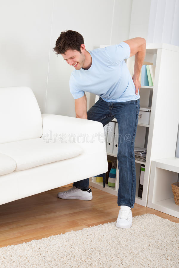 Man in pain lifting couch stock photos