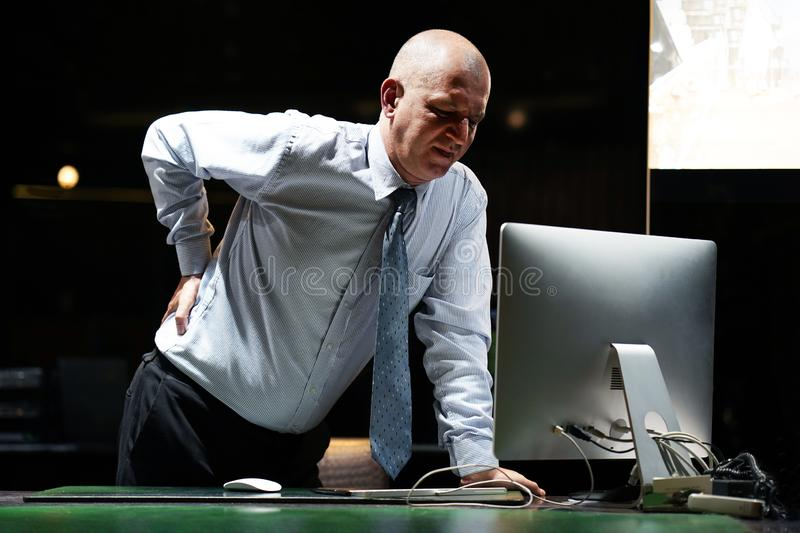 Man, pain at lower back. Close-up view of elderly man-reception worker hotel manager with pain in kidneys. Man with back ache clasping her hand to her lower back royalty free stock photography