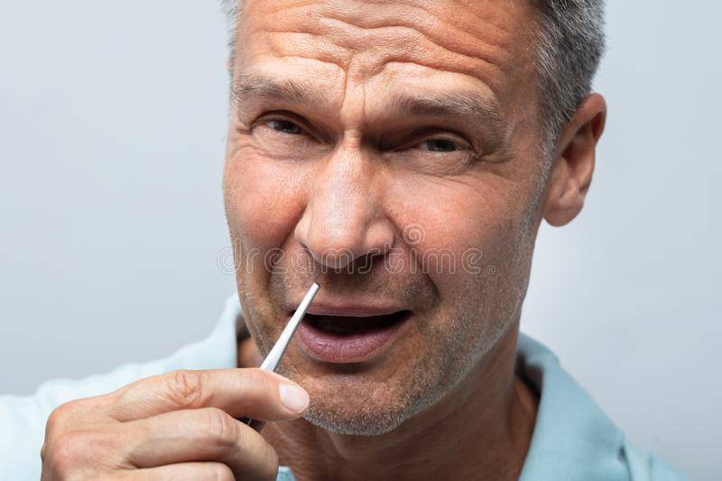 Man In Pain Removing Nose Hair With Tweezers stock image