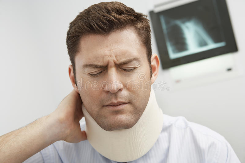Man In Pain Wearing Neck Brace. In hospital stock images