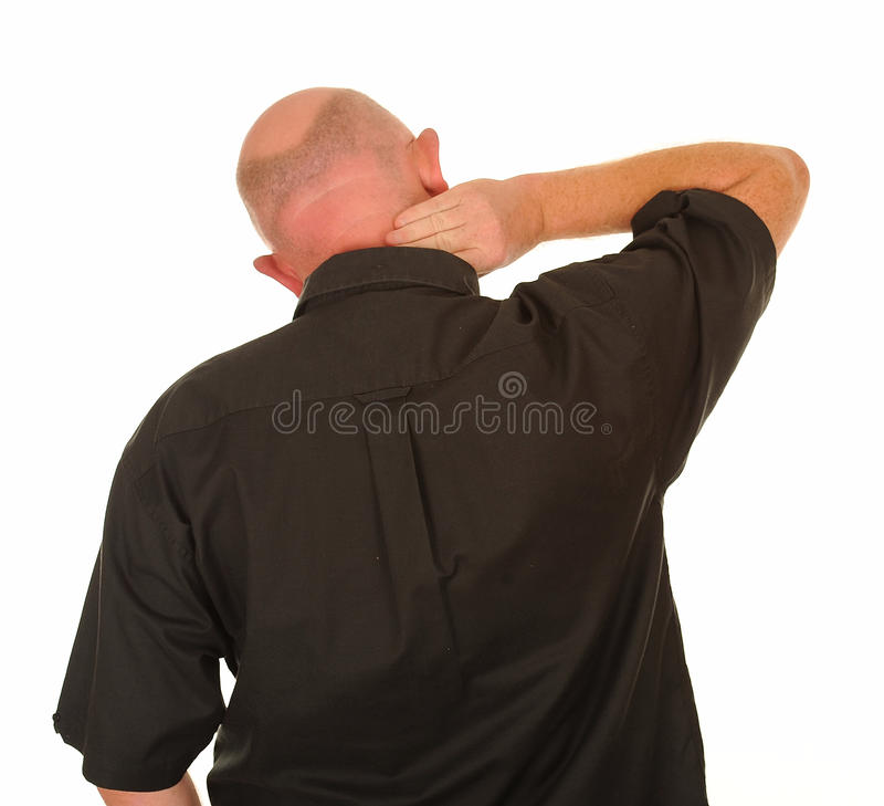 Man with painful neck. Rear view of middle aged man rubbing painful neck, white studio background stock images