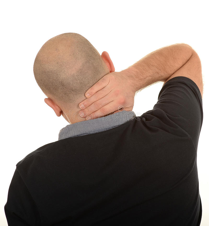 Man with painful neck. Rear view of middle aged man rubbing painful neck, white studio background stock photography
