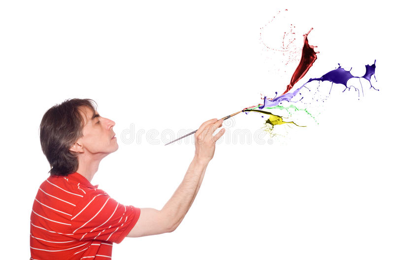 Man with a paint brush. A man with a paint brush that splashes of paint royalty free stock photo