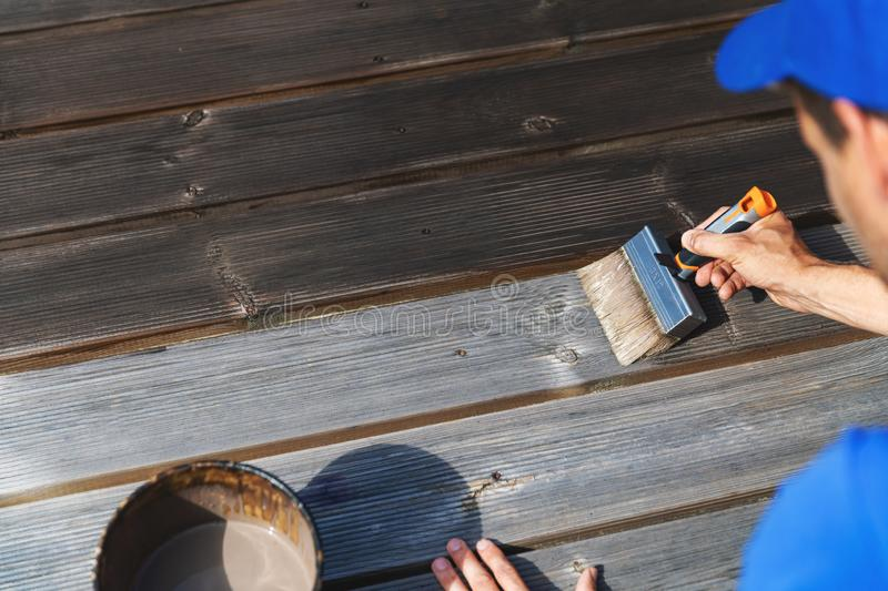 Man restores wooden patio deck with wood protective paint. Man with paintbrush restores wooden patio deck with wood protective paint stock photos