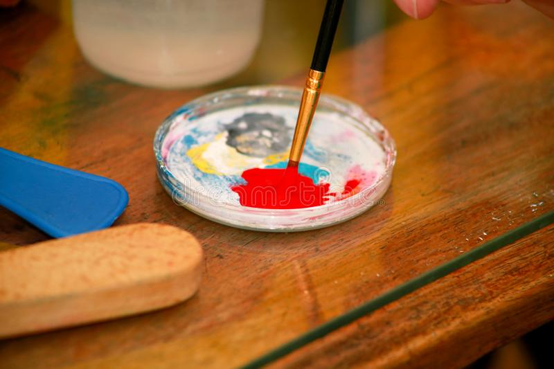 Man painter is mixing colors before painting at art paint studio. Artist in his hand holding paintbrush mixed color oil paints. Man painter is mixing colors royalty free stock photography