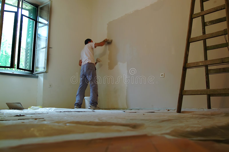 Man painting. Professional painter is painting the room stock image