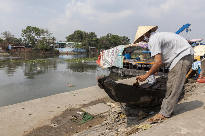 Man painting boat on Mekong river bank stock photo