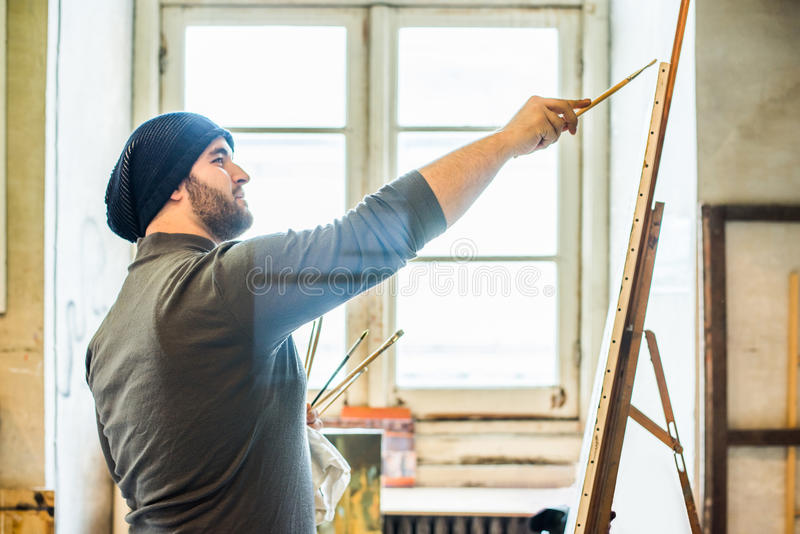 Man painting with brush on a canvas window background. Man wearing a hat and a grey top, painting with brush on a canvas window background stock image