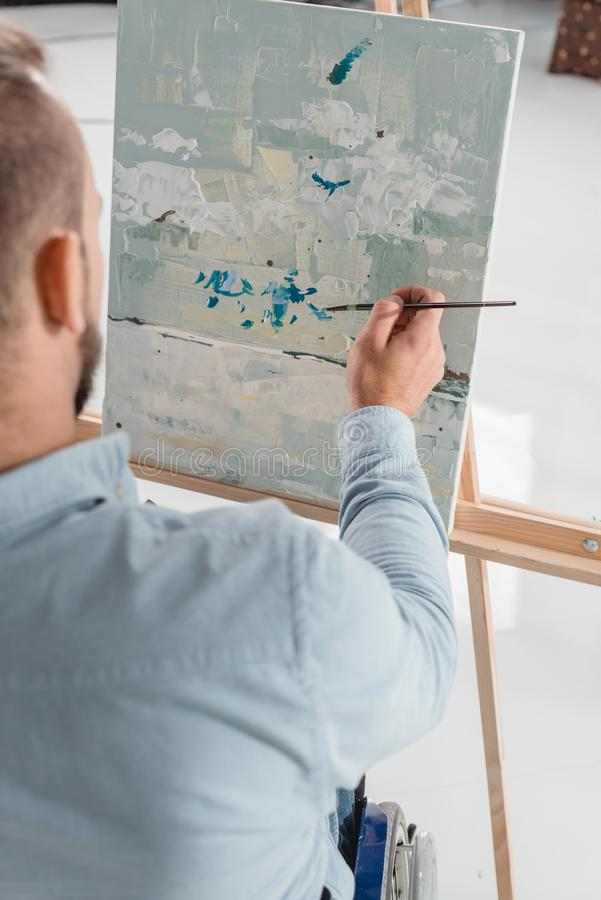 Man painting on canvas. Cropped shot of man painting on canvas with oil paint stock photography