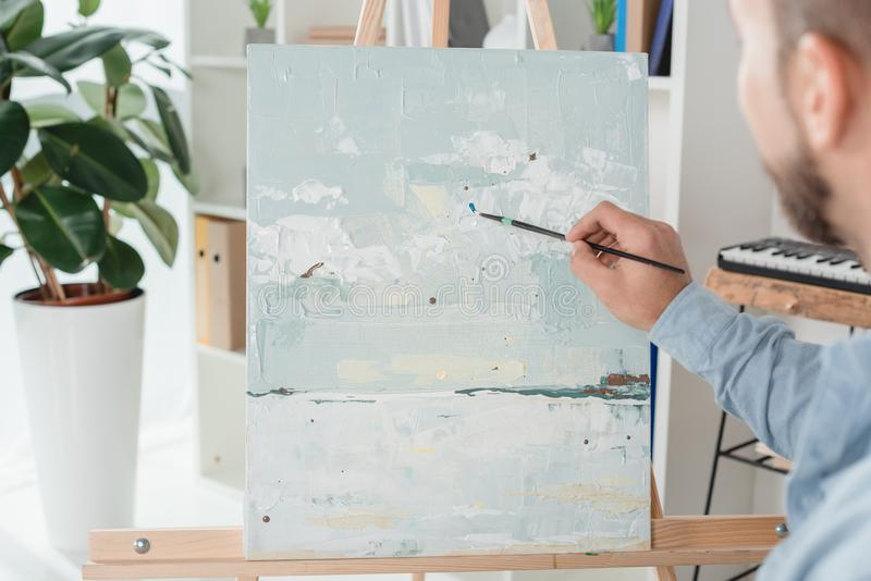 Man painting on canvas. Cropped shot of man painting on canvas with oil paint stock images