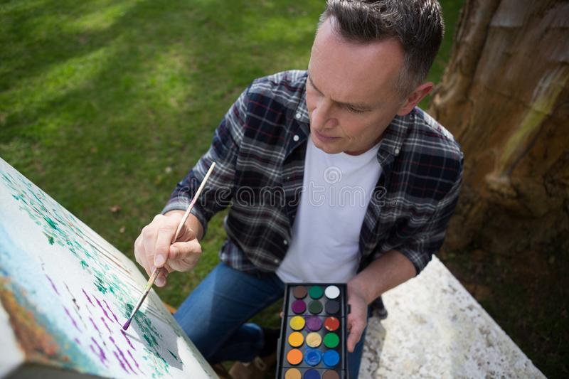 Man painting on canvas in garden. On a sunny day stock photography