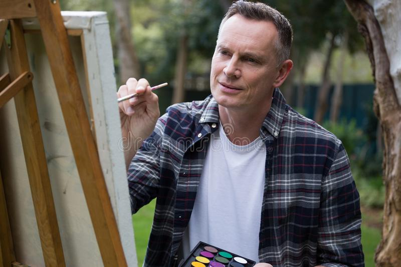 Man painting on canvas in garden. Smiling man painting on canvas in garden royalty free stock photo