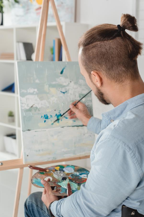 Man painting on canvas. Man painting abstraction on canvas with oil paint royalty free stock photo