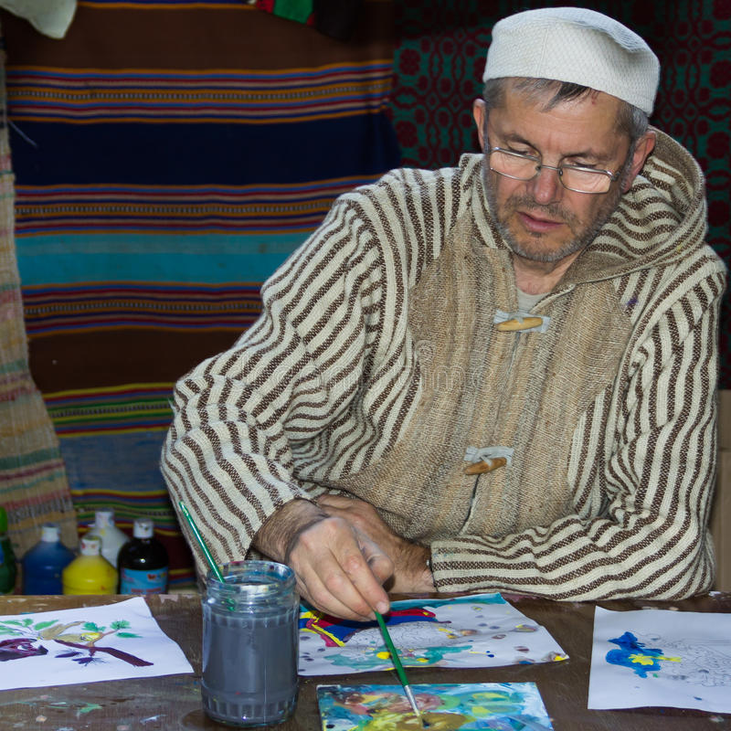 A man painting on paper. In Biblical Village. The Biblical Village is the first project in Europe organized in Bucharest at Titan Park and represents historical royalty free stock images