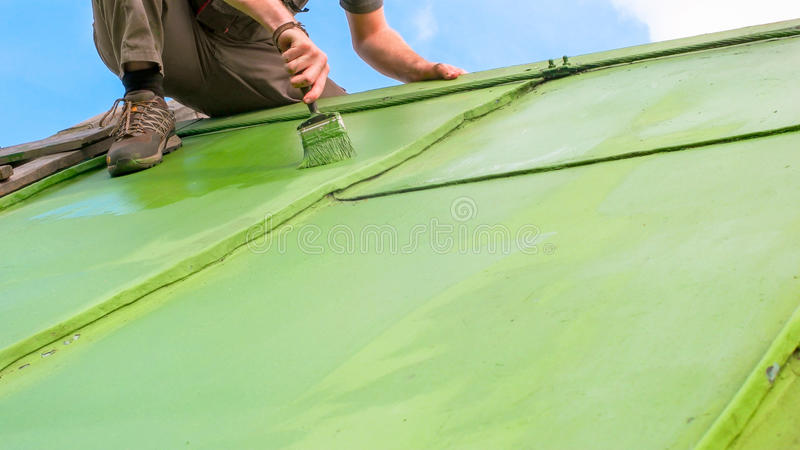 Man Painting Roof from the Top stock images