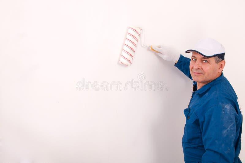 Man painting the wall. Senior man painting the wall royalty free stock image
