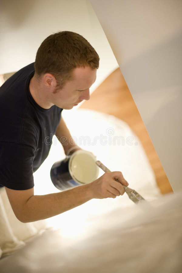 Man painting wall. Young man concentrates painting stairway walls royalty free stock photos