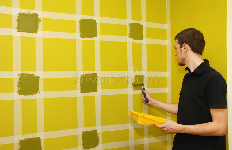 Man painting wall with masking tape. Worker Man painting a wall with masking tape stock photography