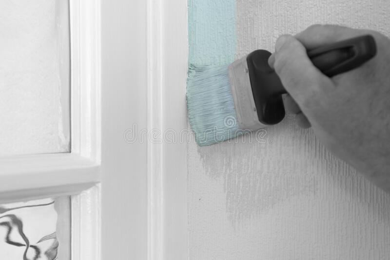 Man painting wall with mint green paint on textured wallpaper,  cutting in against door frame. royalty free stock image