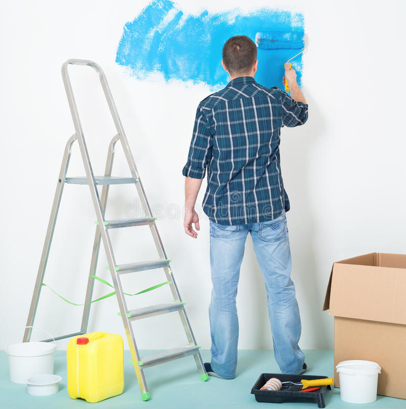 Man painting wall. Young man painting wall at home - building and home concept royalty free stock photos