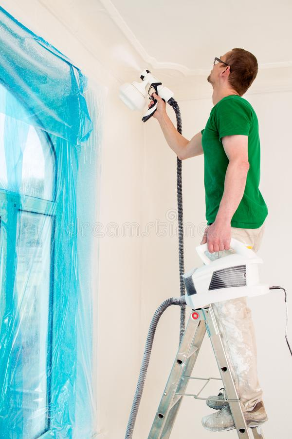 Man painting walls with paint spray gun stock images