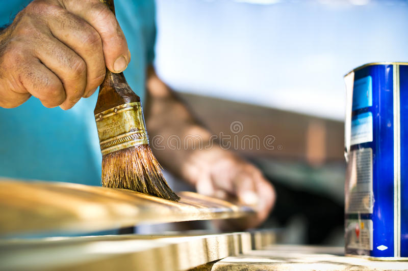 Man painting wood with lacquer natural color. royalty free stock photography