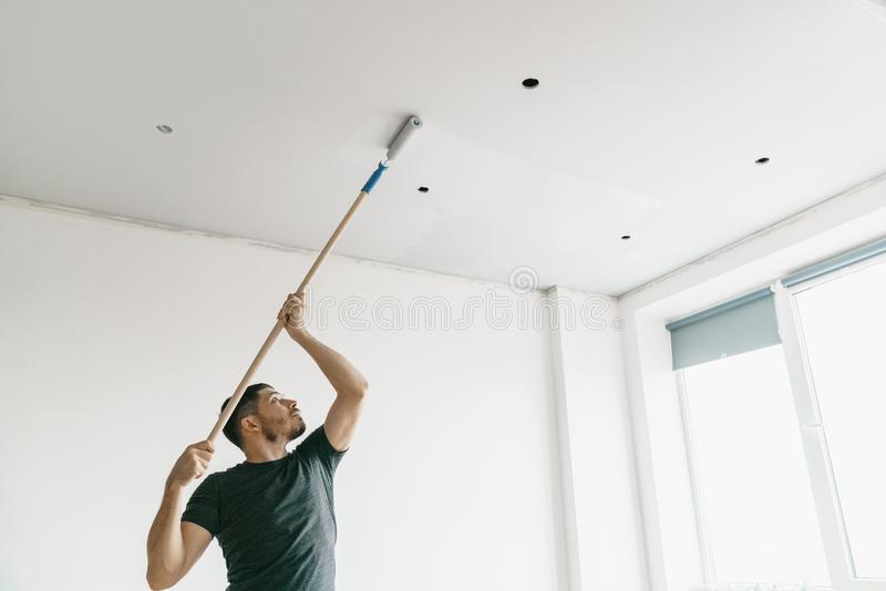 The man paints the ceiling in a gray color with a roller in a bright room. royalty free stock image