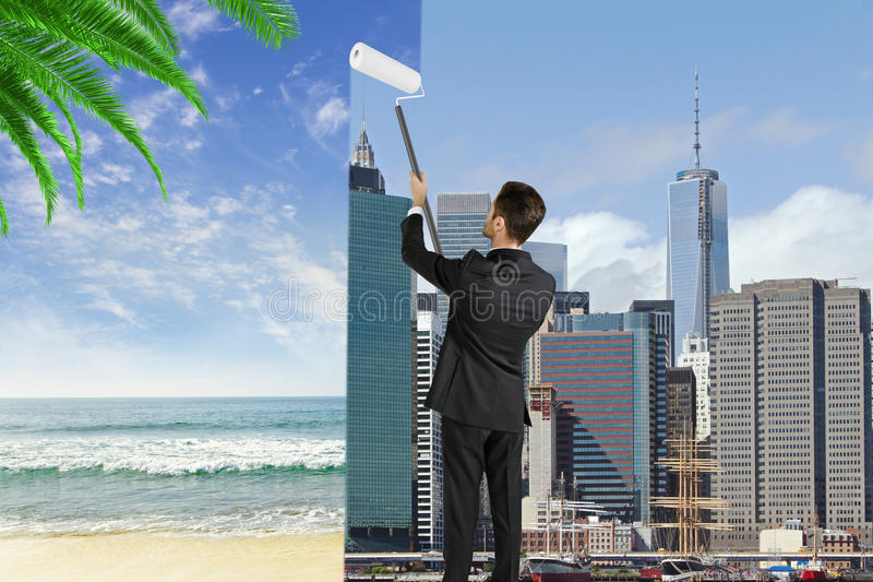 Man paints megapolis city in the beach with ocean, change royalty free stock images