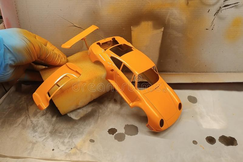 A man paints a scale model car. Paint the spoiler, trunk lid and toy body in a bright orange color. Sports assembly hobby plastic kit modeling modelist vintage royalty free stock image