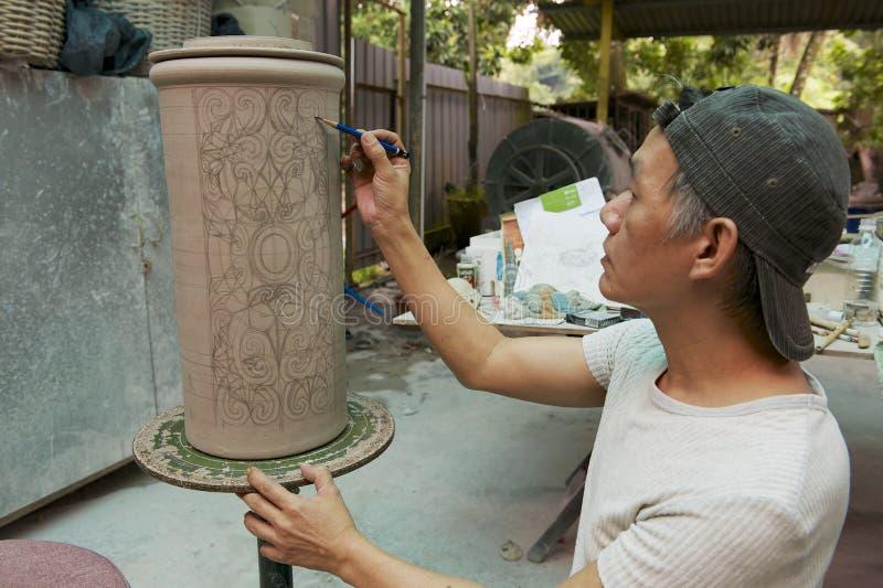 Man paints traditional tribal tattoo motives decoration, Kuching, Malaysia. KUCHING, MALAYSIA - AUGUST 27, 2009: Unidentified man paints traditional tribal stock image