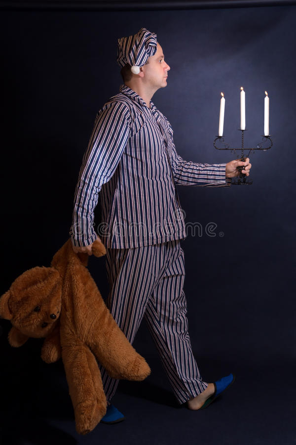 Man in pajamas goes sleep. Man in pajamas walking with a candlestick and teddy bear royalty free stock image