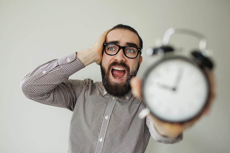 Man in panic holds alarm clock and head in fear of deadline. Man in panic with beard and glasses holds alarm clock and head scared of deadline royalty free stock photography