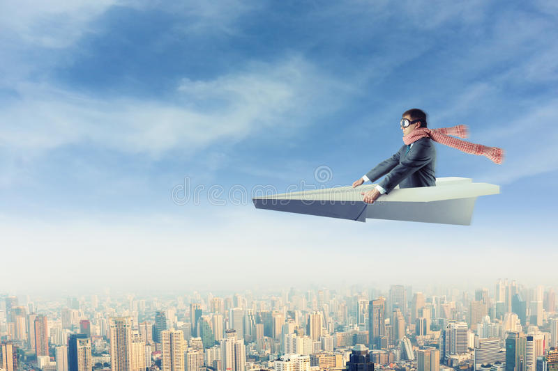 Man on paper airplane above the city. Businessman with the scarf on paper airplane above the city royalty free stock image