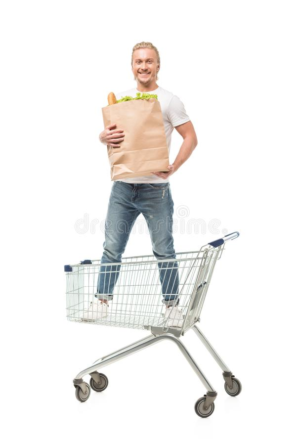 young caucasian man with paper bag standing in shopping cart royalty free stock images