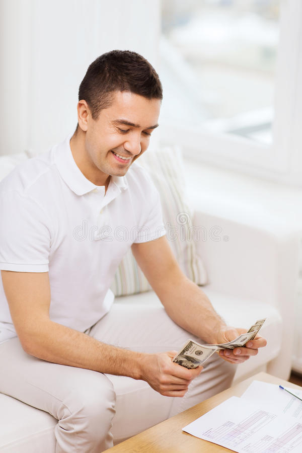 Man with papers and calculator at home stock photography