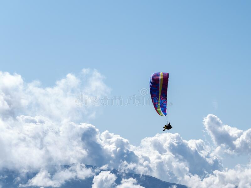 Man on a paraglider on a background of blue sky and clouds royalty free stock image