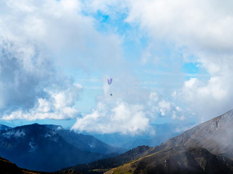 A man on a paraglider flies in the sky over a beautiful mountainous area through a cloud of haze stock photos