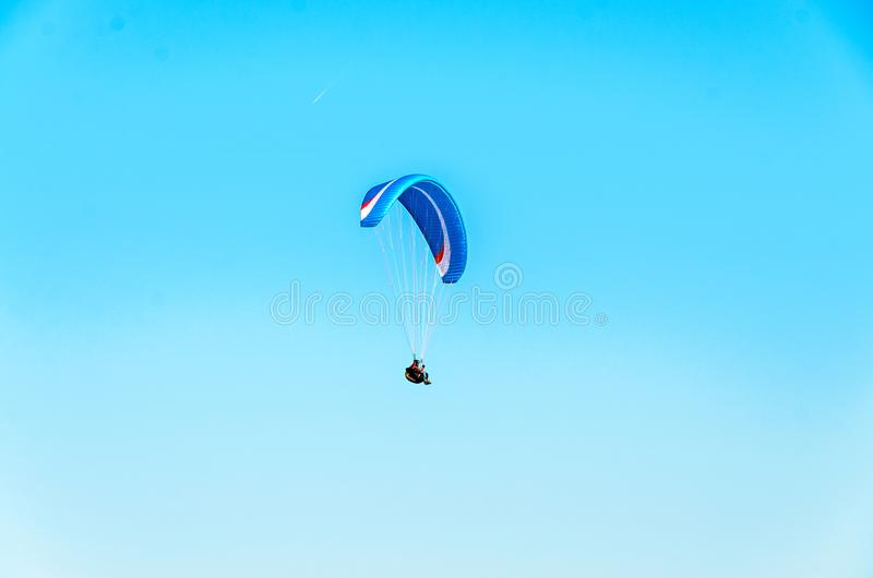 Man paragliding with blue parachute above water sea, clear sky.  royalty free stock image