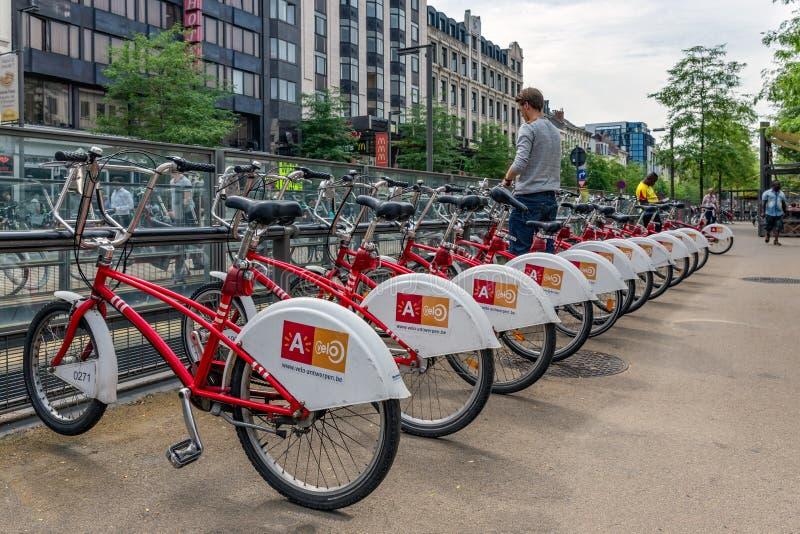 Man parking bicycle at a bicycle rental in Antwerp, Belgium stock images