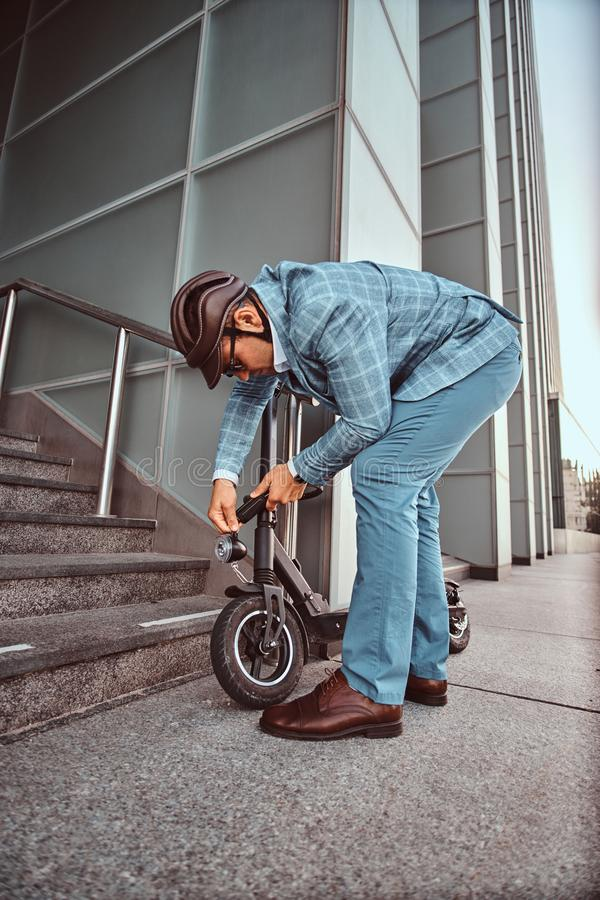 Man is parking his electro scooter and ut chain locker on it royalty free stock image