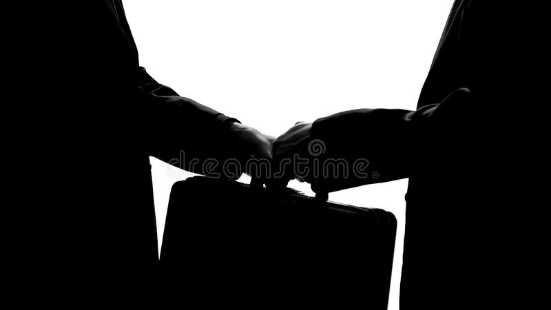 Man passing suitcase to partner, business agreement or financial fraud concept stock images