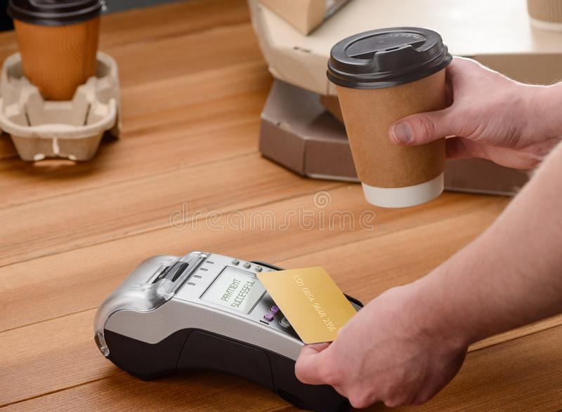 Man paying for coffee. By a credit card, close-up shot. Buying street food with easy contactless payment stock image