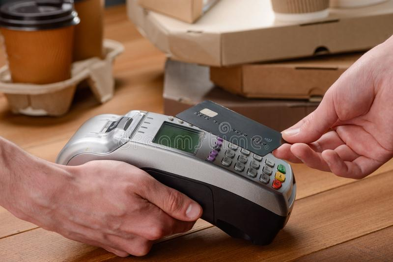 Man paying by card. Man paying for coffee and pizza by card with a single tap. Contactless payment concept stock images