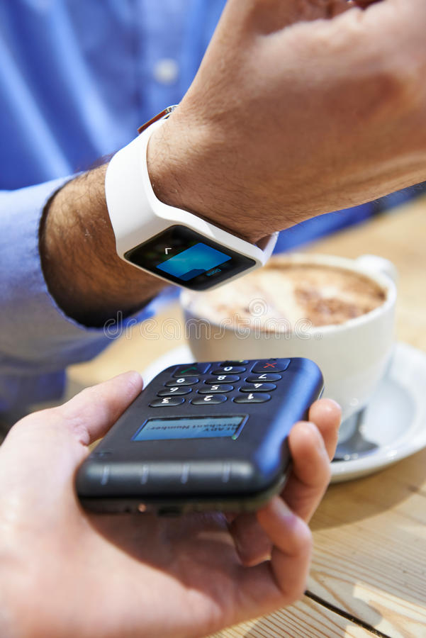 Man Paying In Coffee Shop Using Contactless Payment App On Smart. Man Pays In Coffee Shop Using Contactless Payment App On Smart Watch stock photo