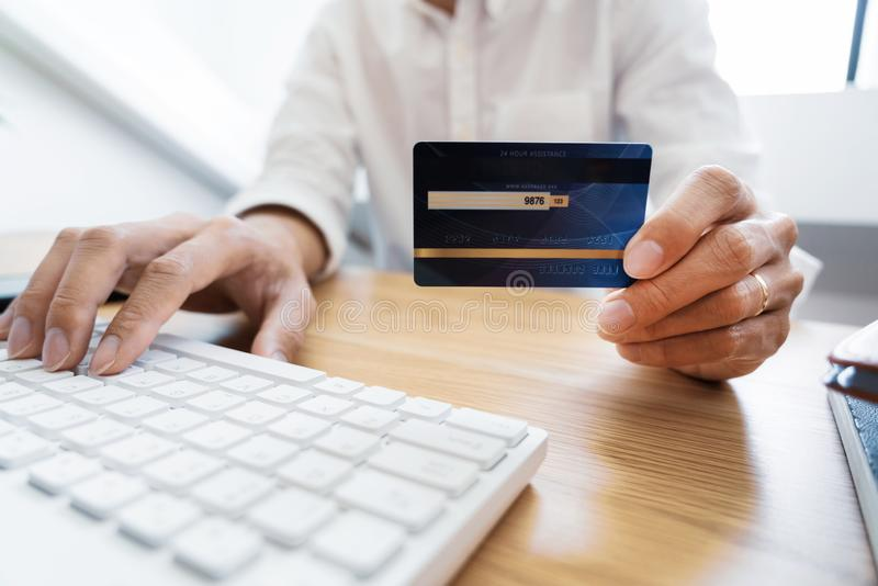 Man paying with credit card and entering security code for online shoping making a payment or purchasing goods on the internet stock images