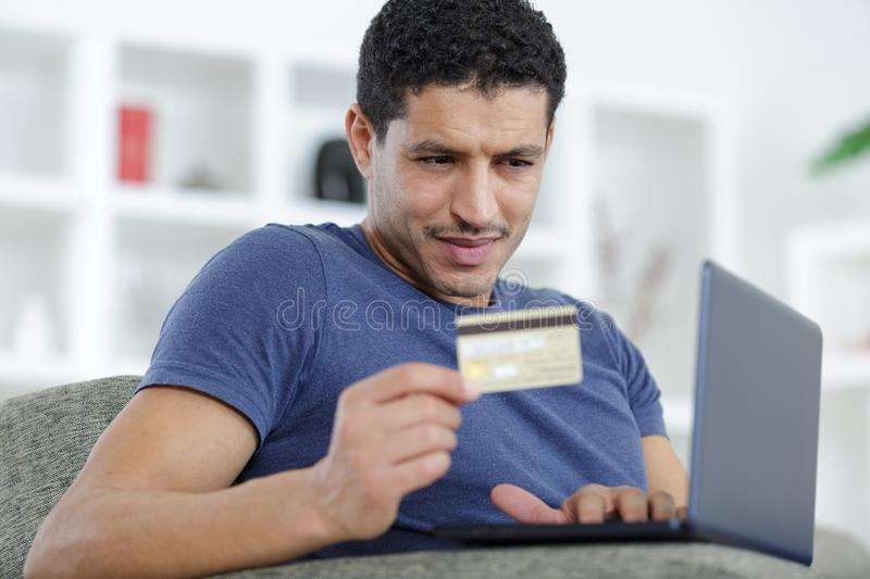 Man paying with credit card on laptop stock images